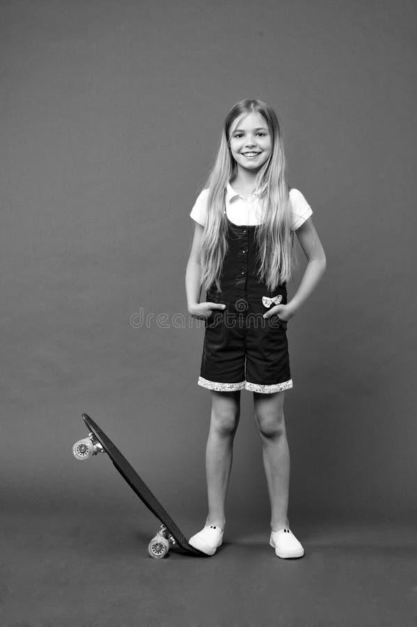 Tonårhobbybegrepp Flicka på att le framsidan som poserar med encentmyntbrädet, violett bakgrund Ungeflicka med långt hår som är k royaltyfri fotografi