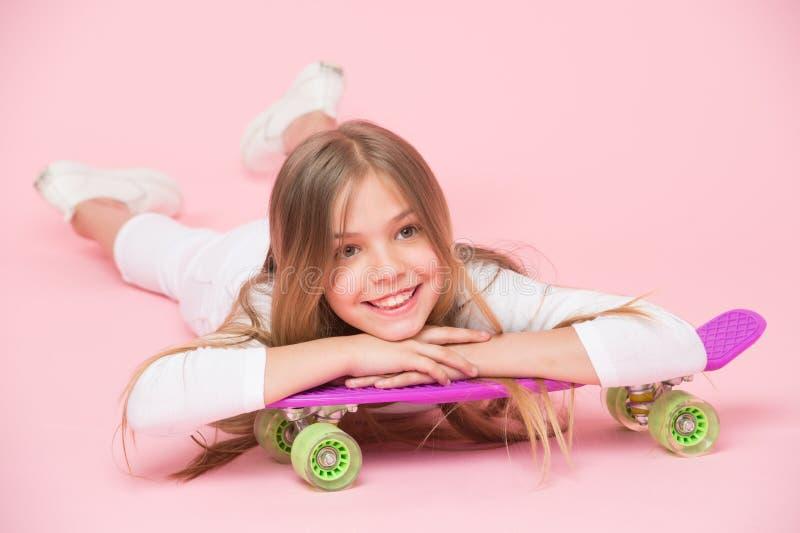 Tonårhobbybegrepp Flickan gillar för att rida skateboarden och sportig livsstil Flicka på att le framsidan som poserar med encent arkivbilder