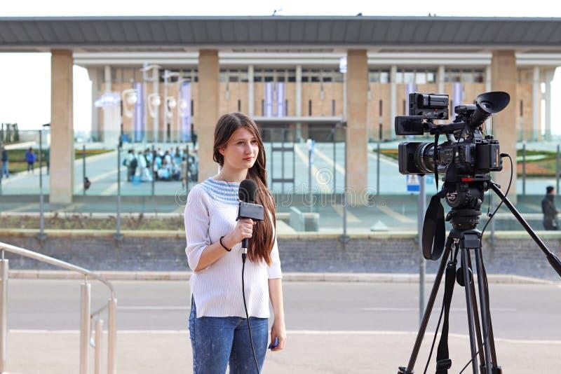Tonårig ålderflickareporter som framme talar av knesst royaltyfria bilder