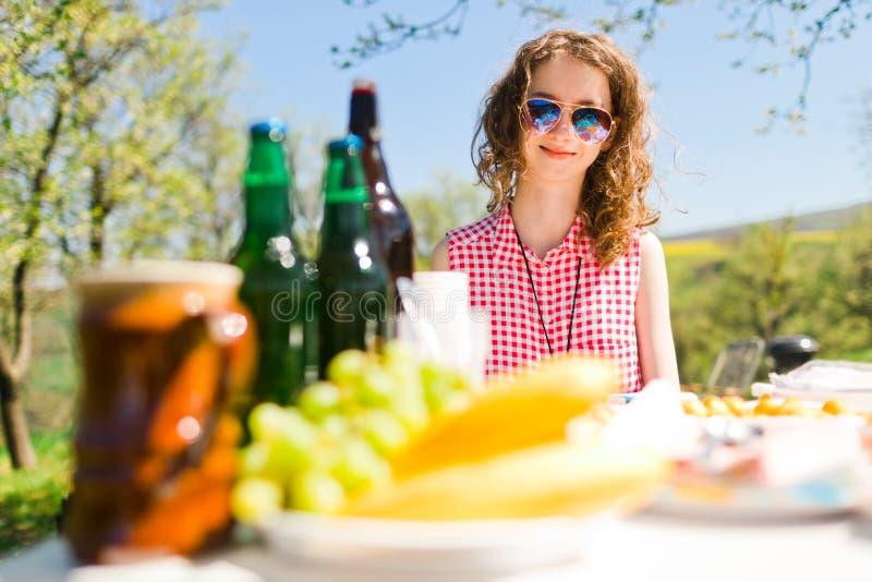 Tonårig åldrig flicka i den röda rutiga skjortan som sitter vid tabellen på trädgårdpartiet - mat och flaskor på tabellen royaltyfria bilder