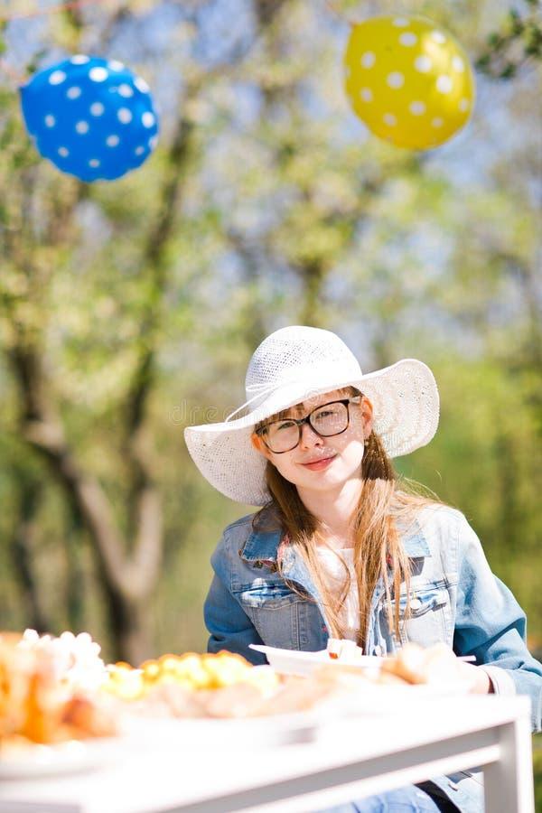 Tonårig åldrig flicka i vit sunhat som sitter vid tabellen på födelsedagen gard royaltyfri fotografi