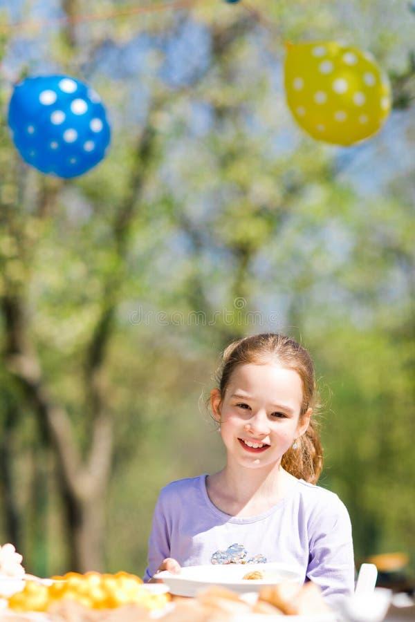 Tonårig åldrig flicka som sitter vid tabellen på födelsedagträdgårdpartiet arkivbild