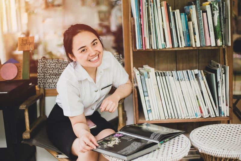 Tonårig enhetlig flicka för asiatiskt universitet läsa en bok arkivfoto