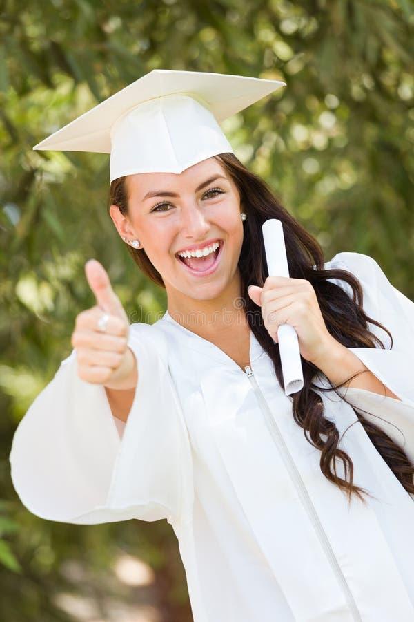 Tonårig flicka för blandat lopp som firar avläggande av examen i lock och kappa arkivfoton