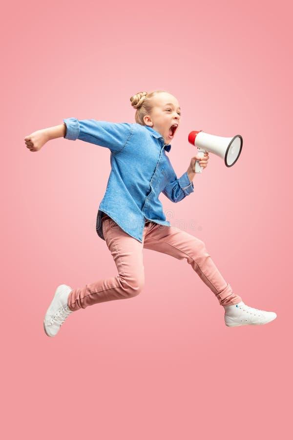 Tonårig flicka för härligt ungt barn som hoppar med megafonen som isoleras över rosa bakgrund royaltyfria foton