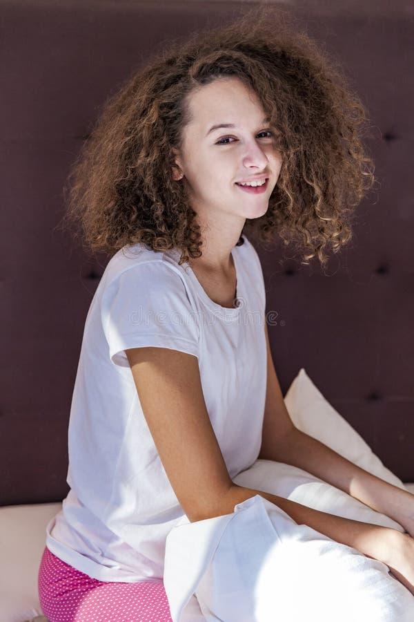 Tonårig flicka för lockigt hår på sängen arkivbilder