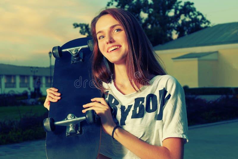 Tonårig flicka för lycklig redhair som poserar med skateboarden arkivbild