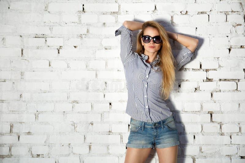 Tonårig flicka för modegatastil på tegelstenväggen royaltyfri fotografi
