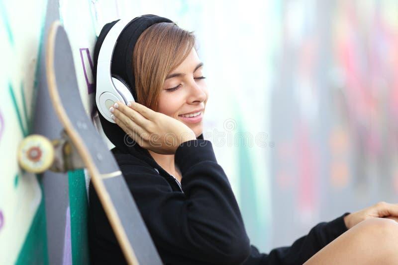 Tonårig flicka för skateboradåkare som lyssnar till musiken med hörlurar fotografering för bildbyråer