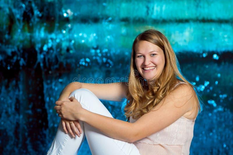 Tonårig flicka framme av den blåa vattenfallet arkivbild