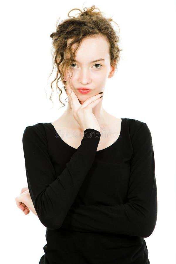 Tonårig flicka i den svarta klänningen som poserar i studio på vit bakgrund fotografering för bildbyråer