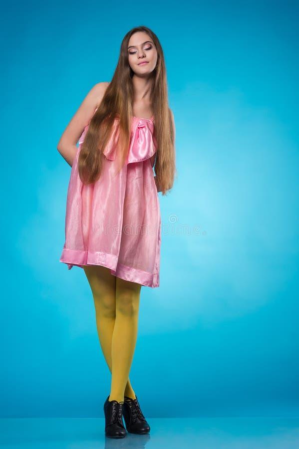 Tonårig flicka i en rosa klänning som poserar med stängda ögon royaltyfri foto