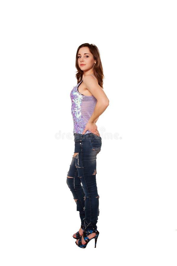 Tonårig flicka i sönderriven jeans. Isolerat på vit royaltyfria foton