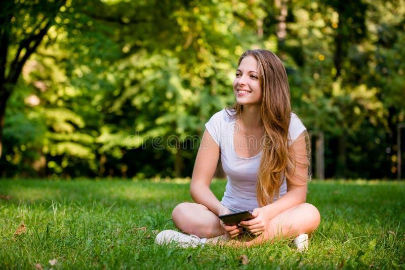 Tonårig flicka med bokavläsaren royaltyfri foto