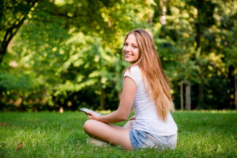 Tonårig flicka med bokavläsaren royaltyfria foton