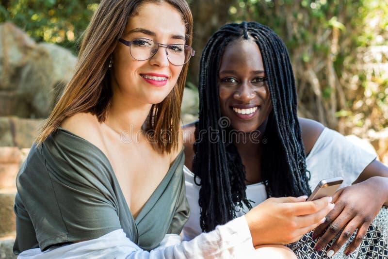 Tonårig flicka med den afrikanska vännen utomhus royaltyfri bild