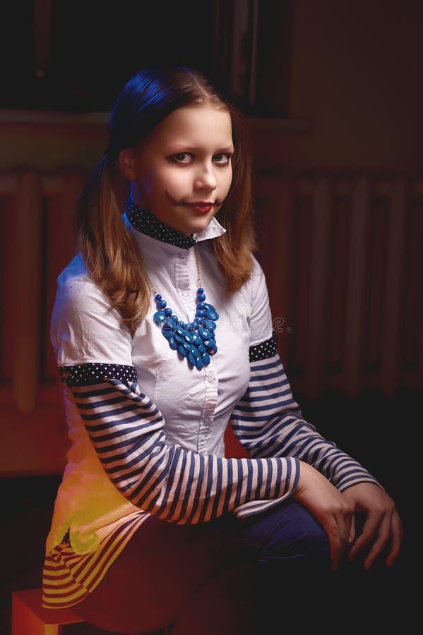 Tonårig flicka med en grina på hennes framsida royaltyfri foto