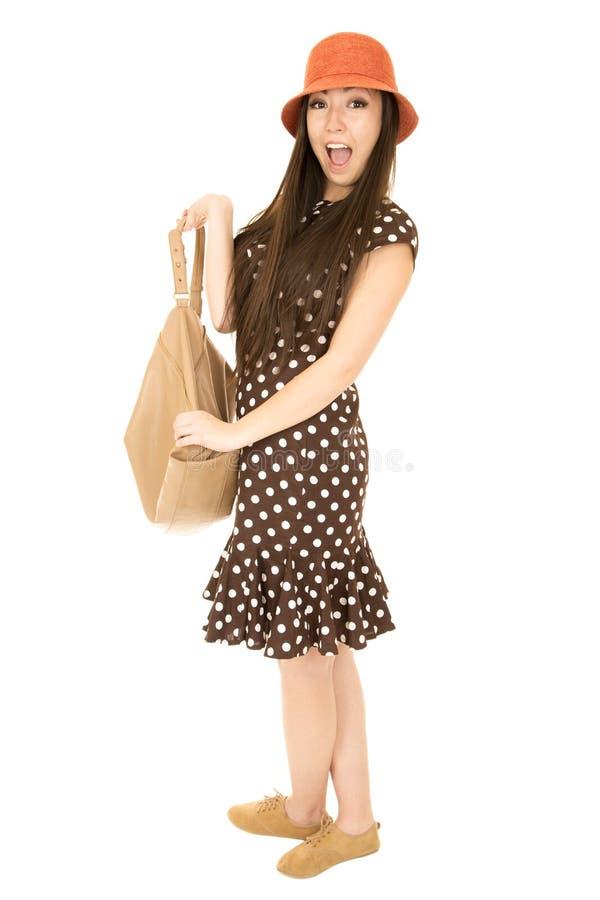 Tonårig flicka med ett lyckligt ansiktsuttryck som rymmer hennes handväska royaltyfri bild