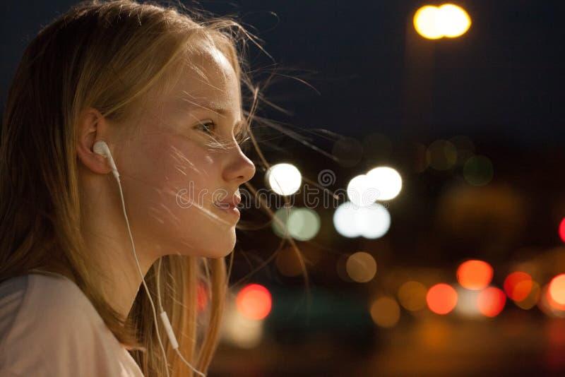 Tonårig flicka med hörlurarståenden lyssnande musiktonåring till Hörlurar drömmer lyckligt royaltyfri bild