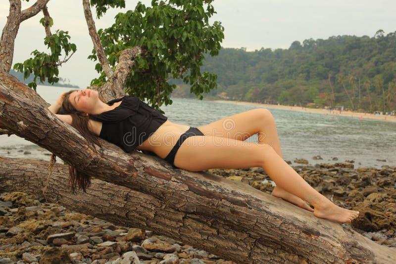 Tonårig flicka med länge vått brunt hår i den fulla kroppen po för baddräkt fotografering för bildbyråer