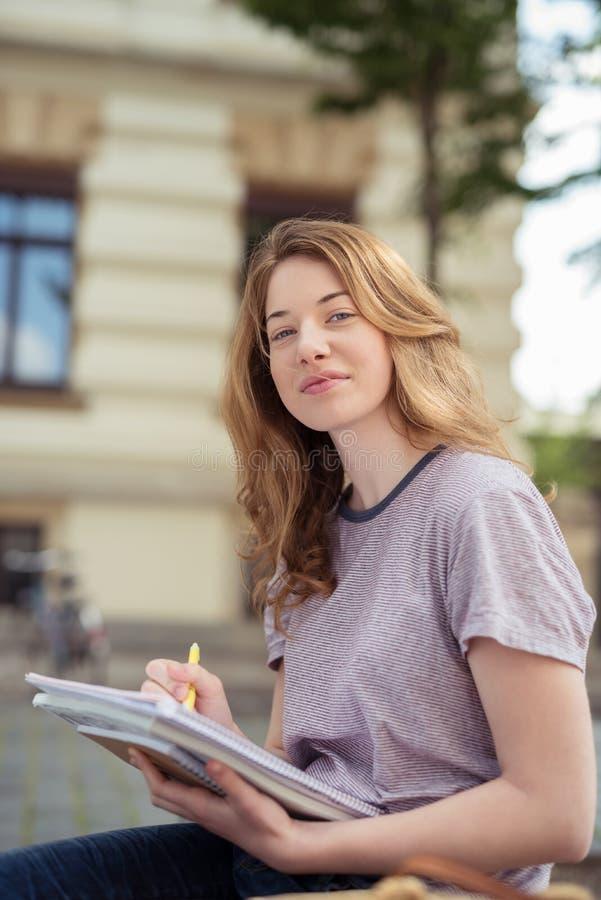 Tonårig flicka med pennan och anmärkningar som ser kameran arkivbilder
