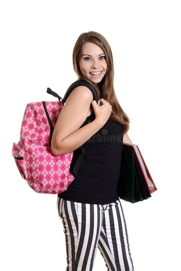 Tonårig flicka med ryggsäcken och skolböcker arkivbilder