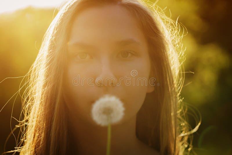 Tonårig flicka som är klar att blåsa maskrosen till kameran fotografering för bildbyråer