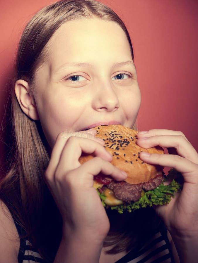 Tonårig flicka som äter en hamburgare arkivfoton