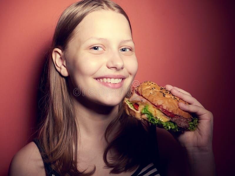 Tonårig flicka som äter en hamburgare fotografering för bildbyråer