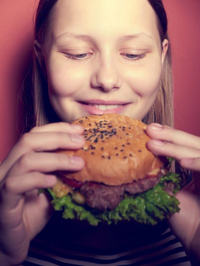 Tonårig flicka som äter en hamburgare arkivbilder