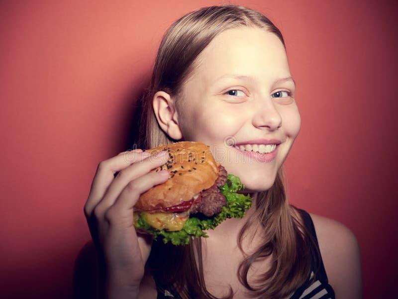 Tonårig flicka som äter en hamburgare royaltyfria bilder