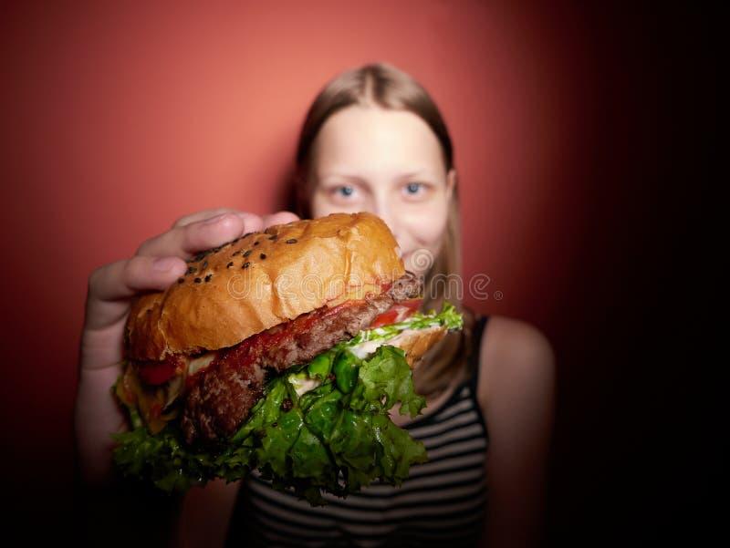 Tonårig flicka som äter en hamburgare arkivfoto