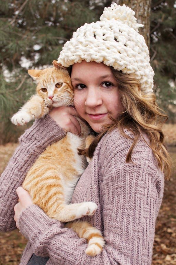Tonårig flicka som bär en virkad hatt som rymmer en kattstående royaltyfri bild