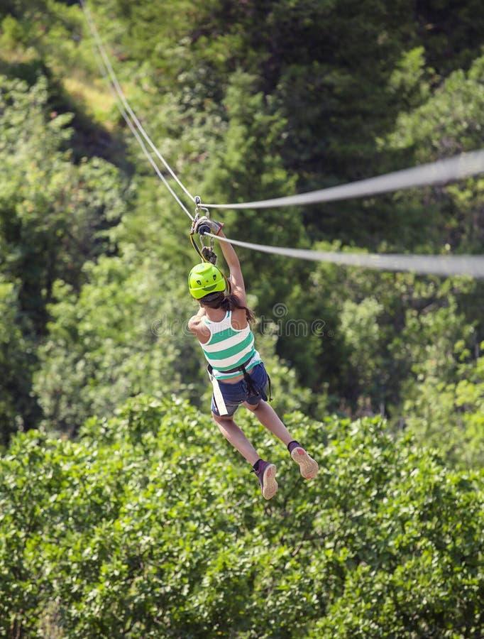 Tonårig flicka som bakifrån rider en zipline till och med skogsikten royaltyfria foton