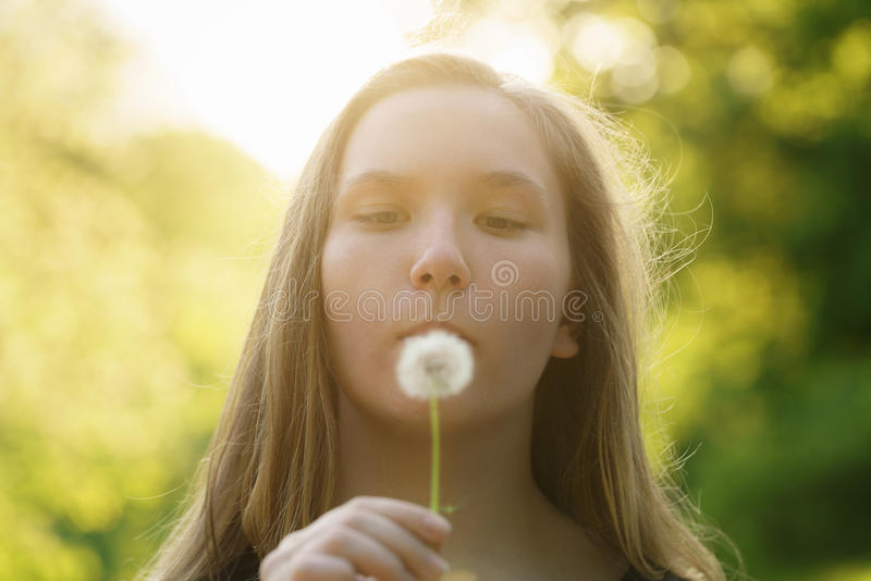 Tonårig flicka som blåser maskrosen till kameran arkivbilder