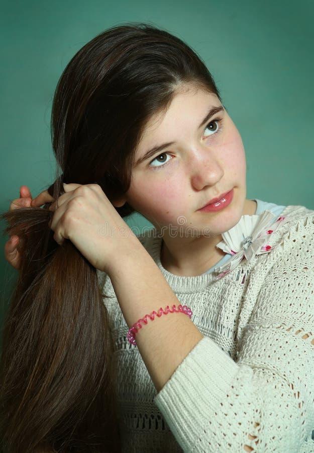 Tonårig flicka som flätar långt brunt tjockt hår royaltyfria bilder