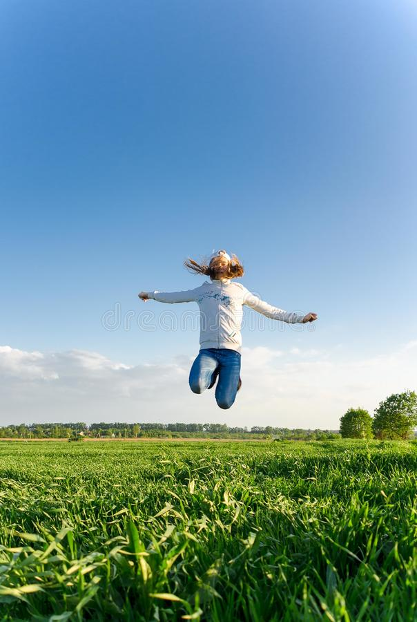Tonårig flicka som högt hoppar i fältet arkivfoto
