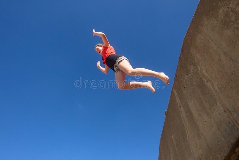 Tonårig flicka som hoppar blå himmel arkivfoto