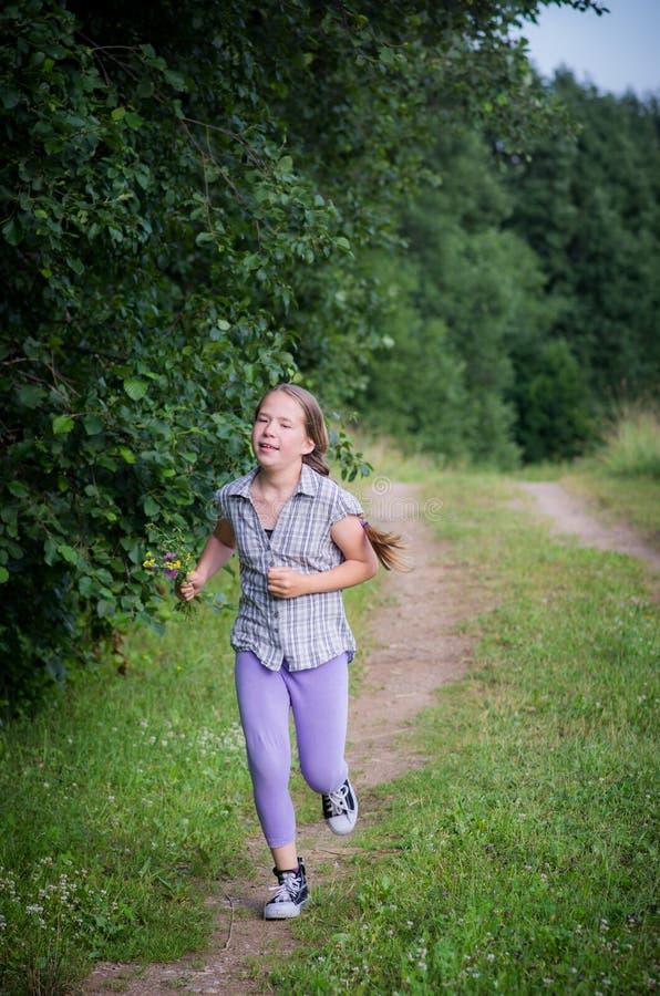 Tonårig flicka som kör i skog royaltyfria foton