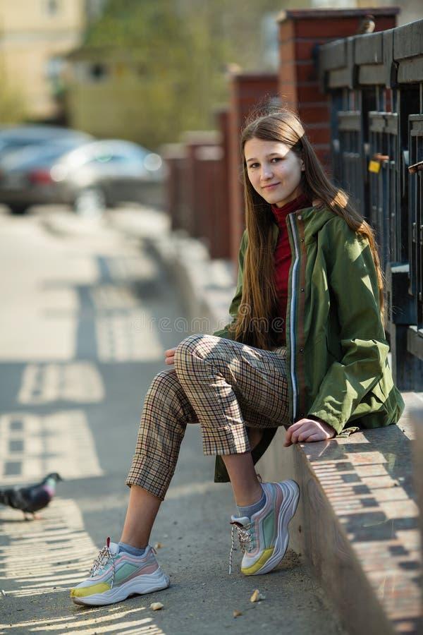 Tonårig flicka som sitter på trottoarkanten på en stadsgata G? royaltyfria foton