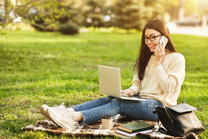 Tonårig flicka som talar på telefonen och använder bärbara datorn royaltyfria foton