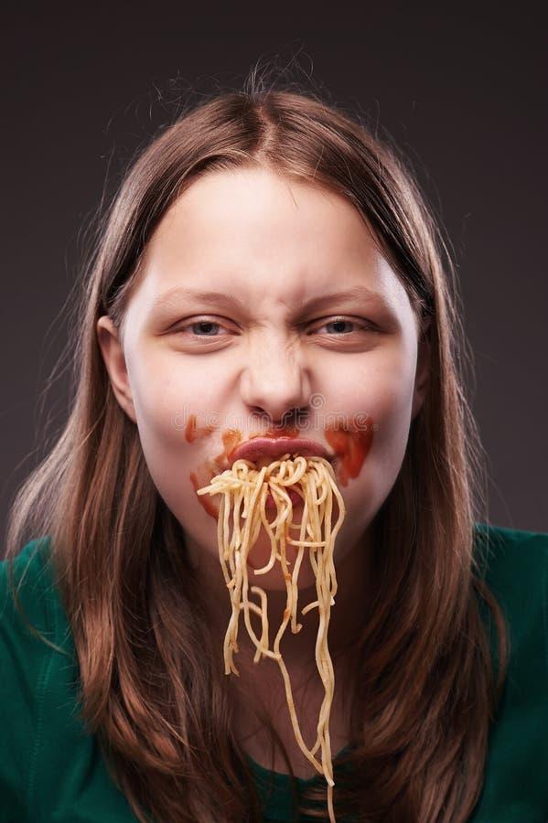 Tonårig flicka som tuggar pasta royaltyfri fotografi