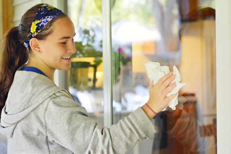 Tonårig flicka som tvättar Windows royaltyfri fotografi