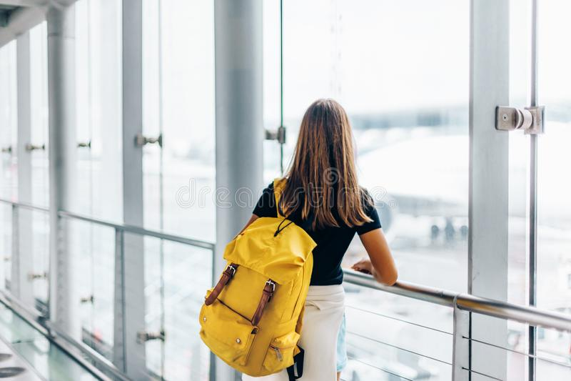 Tonårig flicka som väntar på internationellt flyg i flygplatsavvikelseterminal royaltyfri bild