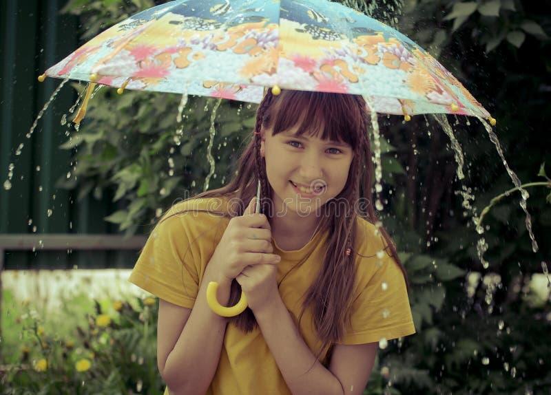 Tonårig flicka under det stora paraplyet royaltyfria bilder