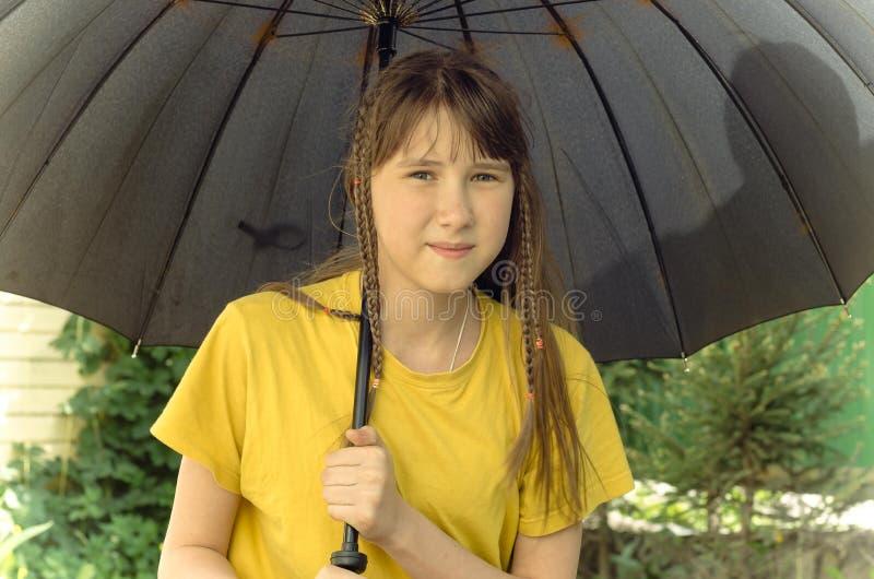 Tonårig flicka under det stora paraplyet arkivbild