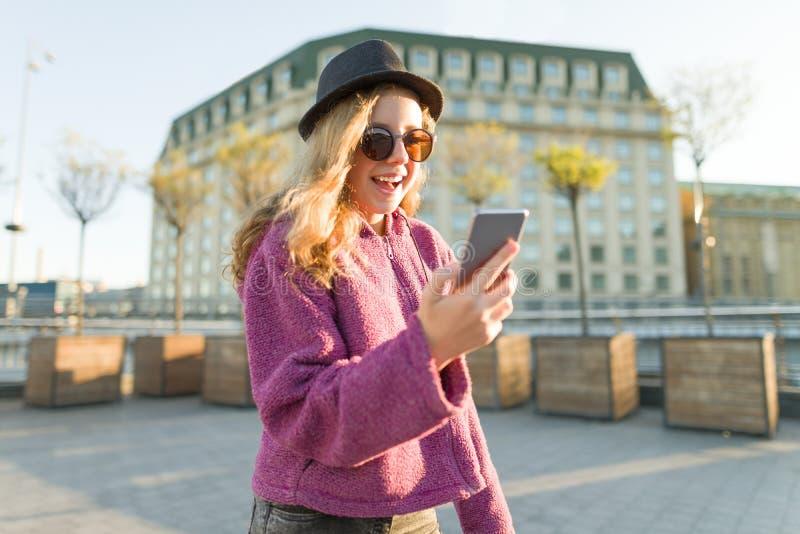 Tonårig flickahipster i hatt och exponeringsglas med mobiltelefonen arkivbilder