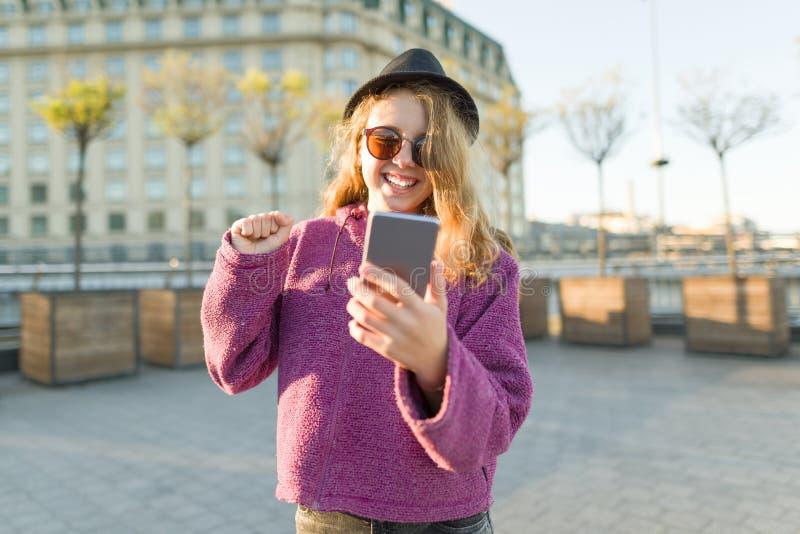 Tonårig flickahipster i hatt och exponeringsglas med mobiltelefonen royaltyfri bild