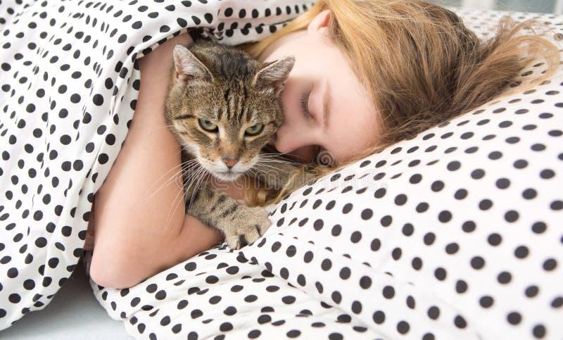 Tonårig flickakramkatt i säng, arkivfoton