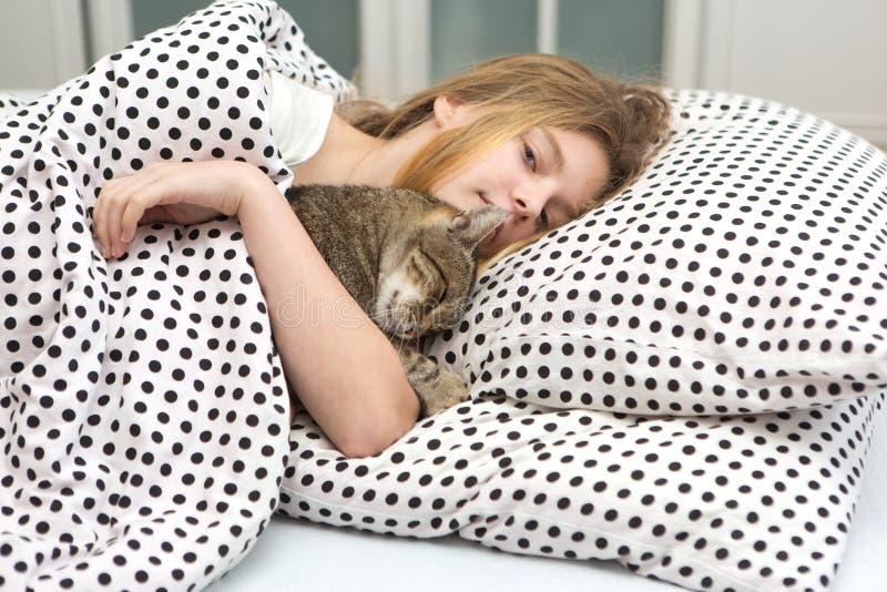 Tonårig flickakramkatt i säng, royaltyfria foton